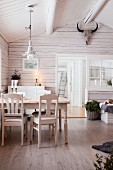 Dining table in wooden cabin with exposed roof structure