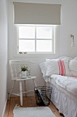 White wooden chair and metal basket below window and next to bed