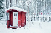 Small red wooden cabin in snowy woods