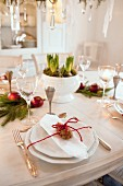 White place setting with silver cutlery and red cord around pine cone on festively decorated dining table