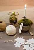 Stillleben mit Papiersternen, Schnurknäuel und brennender Christbaumkerze in Gefäß mit Moos