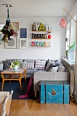 Grey couch and String shelves in cosy living room with retro ambiance