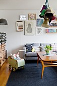 Grey couch and vintage dolls' pram in cosy living room with retro ambiance