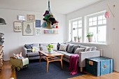 Grey couch, collection of scatter cushions and vintage dolls' pram in cosy living room with retro ambiance