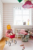 Diamond-patterned wallpaper and red retro dolls' pram in girl's bedroom