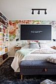 Black letter board with white peg letters on floral textile wallpaper and retro shelving in bedroom