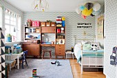 Patterned wallpaper, toys and retro cabinet in boy's bedroom with Scandinavian retro ambiance