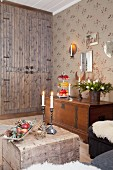 Fitted cupboard, wooden trunk and Advent arrangement in rustic living area