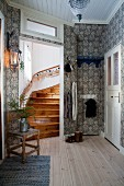 Patterned wallpaper, wooden floor and home-made Advent calendar on handrail of stair in traditional hallway