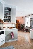 Country-house kitchen with view of cot and traditional long-case clock in living area