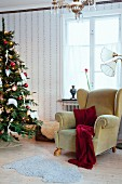 Comfortable wing-back chair next to Christmas tree in vintage-style interior