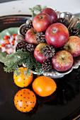 Äpfel, Zapfen und Tannengrün neben mit Nelken gespickten Orangen