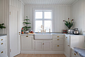 Ceramic sink and wood-clad walls in Swedish country-house kitchen