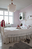 Metal bed with loose cover and ruffles in child's bedroom with pale pink walls