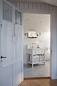 View through lattice door with curtain into white bathroom with wood-panelled walls