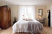 Schlafzimmer im Landhausstil mit niedriger Decke und Holzboden