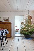 Geschmückter Weihnachtsbaum im Korb in niedriger Stube