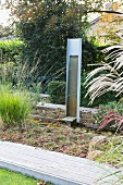 Modern metal fountain, stream and heathers in autumnal garden