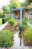 Straight stream leading to wooden house between flowerbeds