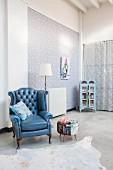 Antiker, blauer Ledersessel auf Betonboden in Loftwohnung mit Blumentapete und Vintage Geschirrschrank