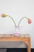 Retro Kaffeekanne mit zwei Tulpen auf rustikaler Holzbank