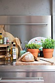 Bread on wooden chopping board and herbs in terracotta pots on stainless steel worksurface