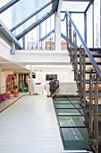 Toys, TV and glass floor on gallery with steel stairs leading to second gallery with glass roof