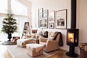 Fire in log-burning stove, pale sofa set and decorated Christmas tree in living room