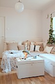 Scatter cushions on corner sofa and candles arranged on white trunk in Scandinavian living room