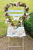 Heart-shaped wreath decorated with flowering bulbs on garden chair