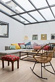 Rocking chair, upholstered stool and corner sofa with various scatter cushions in living area with glass ceiling