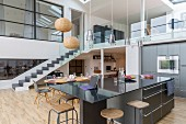 Black counter and gallery with glass balustrade in open-plan kitchen of loft apartment