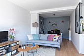 Comfortable sofa, TV cabinet and dining area in background in open-plan apartment