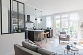 Offener Wohnbereich mit Raumteiler-Verglasung, schwarzer Einbauküche und Küchentheke