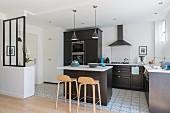 Schwarze Einbauküche mit weißer Thekenplatte in hellem Apartement