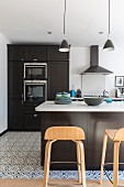 Black fitted kitchen with white worksurface and designer bar stools