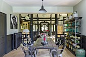 Eclectic furnishings in half-timbered house with open metal shelves, rustic table and classic chairs