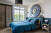 Schlafzimmer mit petrolfarbener Wandgestaltung und passender Bettwäsche, rundes Kunstobjekt als Wanddekoration
