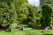 Wooden deckchair in green garden with various trees, pond and rustic bridge