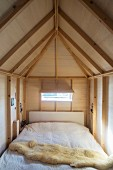 Sheepskin blanket on bed in wood-clad niche below exposed ceiling beams