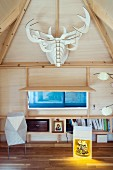 Fitted shelving, lift-up shutter and stylised hunting trophy in converted attic