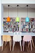 weiße Tischplatte und bunte Pendelleuchten vor rosafarbenem Bücherregal