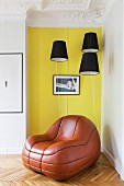 Leather lounge chair below black lampshades against yellow wall in restored period apartment
