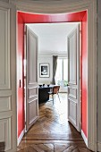 View through red door frame and open panelled double doors into dining room of period apartment