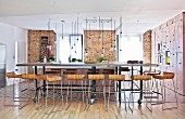 Designer bar stools at long dining table on castors in open-plan interior