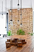 Dining table made from reclaimed materials below pendant lamps made from recycled glass