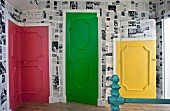 Colourful panelled doors on landing with black and white newspaper-style wallpaper