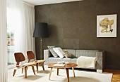 Klassikerstuhl mit Coffeetable, Sofa und Stehleuchte vor brauner Wand im Wohnzimmer