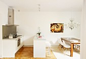 Wooden table and Eames chairs in white designer kitchen with dining area