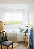 Double bed, white roller blind on window and chair in foreground in bright bedroom